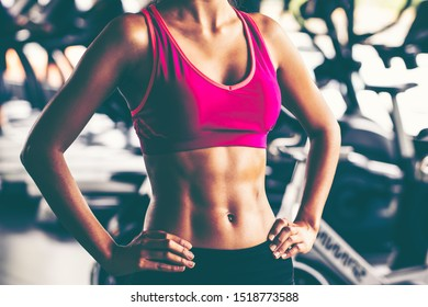 Close-up of a woman's body bodybuilder in the gym. Portrait of muscular woman showing Strong abs on professinal gym background. Beautiful abdominal muscle.