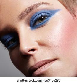 closeup of a woman's eye with a blue eyeshadows