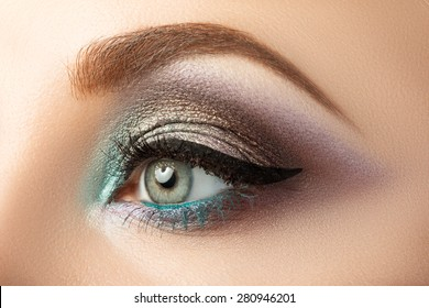 Close-up of woman's eye with creative modern make-up. Smoky eyes and arrow.