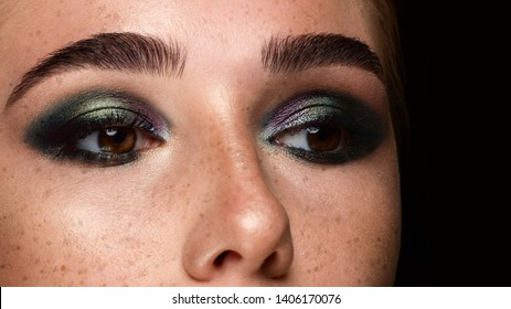 Close-up of woman's eyes with evening make-up. Fashionable shades of eye shadow, extremely long eyelashes and thick smooth eyebrows. Open beautiful look. Clean skin and freckles on face