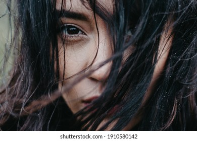 Close-up woman's face with hair fluttering in the wind. Raindrops on your hair. Shallow depth of field