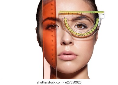 Close-up of a woman's face measure rulers before a plastic surgery to change the proportions. Isolated on white background