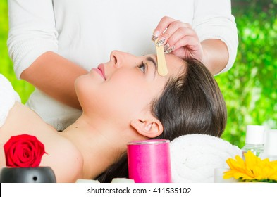 Closeup womans face receiving facial hair waxing treatment, hand using wooden stick to apply wax, beauty and fashion concept