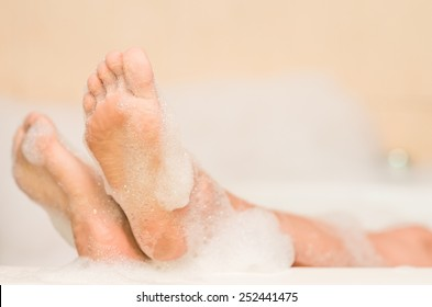 closeup of woman's feet covered with foam bubble bath