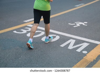 Closeup of woman's feet jogging in running track on the road in the evening. The good health promotion activity.