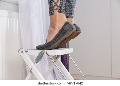 Closeup of woman's feet and legs standing on step ladder