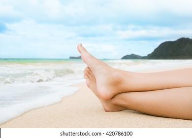 Closeup of woman's feet relaxing on a tropical beach in Hawaii.