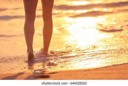 Closeup of woman's feet walking on the beach during a golden sunset.