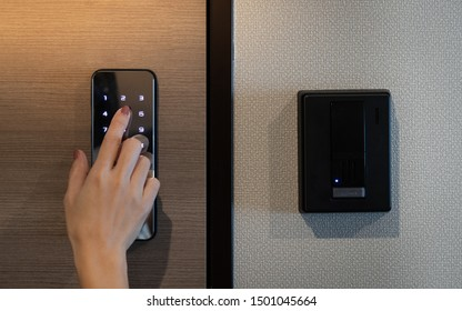 Closeup of a woman's finger entering password code on the smart digital touch screen keypad entry door lock in front of the room. Self Check-in, Airbnb, Modern security, Keyless, Temporary codes.