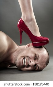 Closeup of a woman's foot crushing man's head