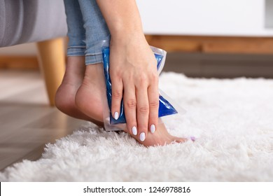 Close-up Of A Woman's Hand Applying Ice Gel Pack On Her Ankle