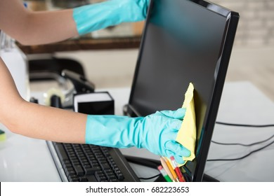 Close-up Of A Woman's Hand Cleaning The Desktop Screen With Yellow Rag In Office