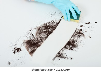 Close-up of woman's hand cleaning dirt on table with sponge at home