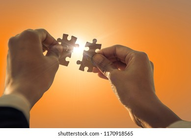 Closeup of a woman's hand connected to jigsaw puzzles and with soft light communicating to successful work, Business solutions, Success and strategy concept.