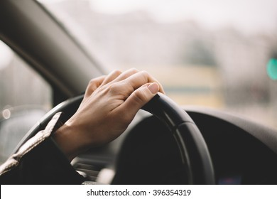 Close-up of a woman's hand driving a car