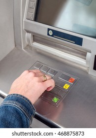 Closeup of woman's hand entering PIN code on ATM machine keypad
