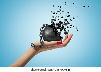 Closeup of woman's hand facing up and holding black wall and chain dissolving into pieces, on light-blue background. Gain liberty. Pay out debts. Cope with difficulties.