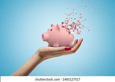 Close-up of woman's hand facing up and holding cute pink piggy bank that has started to disintegrate into pieces on light-blue background. Money worries. Financial difficulties. Profit loss.
