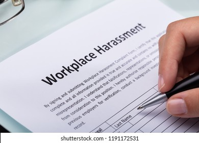 Close-up Of A Woman's Hand Filling Workplace Harassment Form
