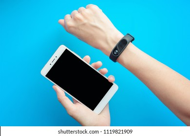 Closeup of woman's hand with fitness tracker and smartphone on blue background