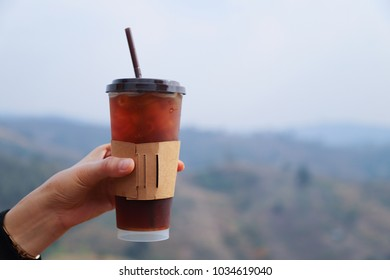 Closeup of woman's hand hold cup of americano ice coffee with mountain view background