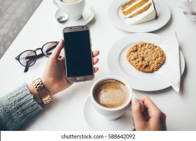 Close-up of woman's hand holding cell phone while drinking coffee and eating oat cookie. Reading news, surfing the web / internet,chatting in social network in smartphone. Blurred background.