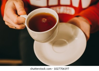 Close-up of a woman's hand holding a cup of hot tea