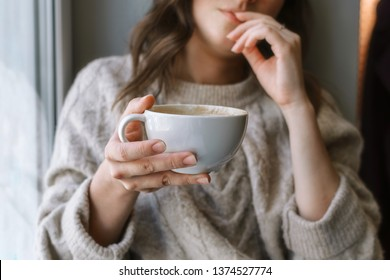 Closeup of woman's hand holding cup with latte in front of the window, shallow selective focus
