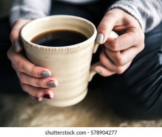 Close-up of a woman's hand holding a cup of hot coffee. fashion, leisure