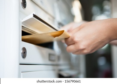 Close-up of woman's hand holding envelope and inserting in mailbox