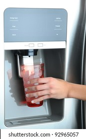 Closeup of a womans hand holding a glass to the water and ice dispenser of a modern refrigerator