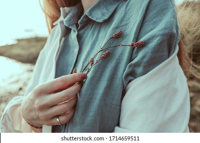 A close-up of woman's hand holding a wild flower. A young ginger woman standing by the lake shore in summertime. A red headed girl wearing i linen aquamarine blouse and linen white jacket.