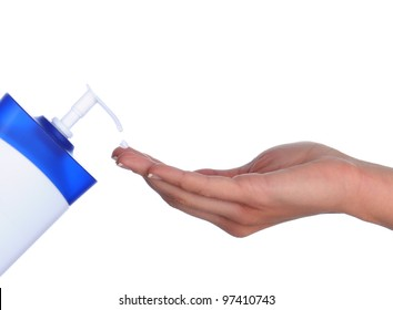 Closeup of a woman's hand and lotion bottle with a drop of cream on one finger. Horizontal format over a white background.