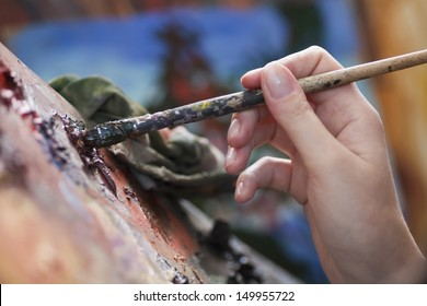 Closeup of a woman's hand mixing colours on art palette with paintbrush
