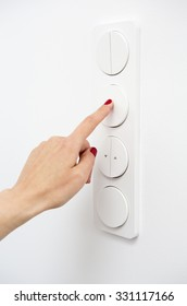 closeup of woman's hand on a light switch