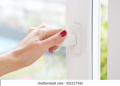 closeup of woman's hand opening a window