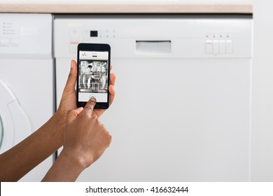 Close-up Of Woman's Hand Operating Dishwasher With Mobile Phone In Kitchen