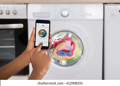Close-up Of Woman's Hand Operating Washing Machine With Mobile Phone In Kitchen