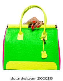 closeup of the woman's hand with orange art manicure, holding green neon handbag isolated on white studio background