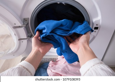 Close-up Of A Woman's Hand Putting Dirty Blue Cloth Into Washing Machine