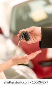 Closeup of woman's hand receiving car keys from agent