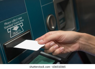 Closeup of woman's hand receiving ticket from self service machine