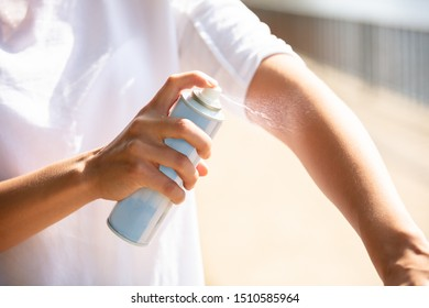Close-up Of A Woman's Hand Spraying Anti Insect Deet Spray On Skin Outdoors