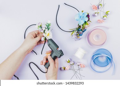 Close-up of woman's hand sticking the flowers on hairband with electric hot glue gun on white backdrop