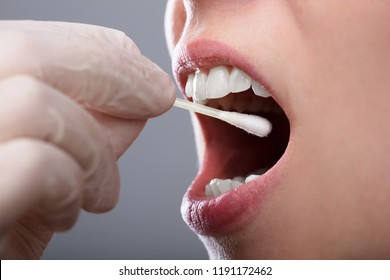 Close-up Of A Woman's Hand Taking Saliva Text From Her Mouth