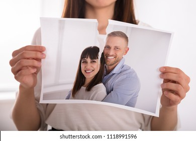 Close-up Of A Woman's Hand Tearing Photo Of Happy Couple