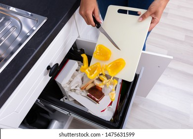 Close-up Of A Woman's Hand Throwing Vegetables In Trash Bin
