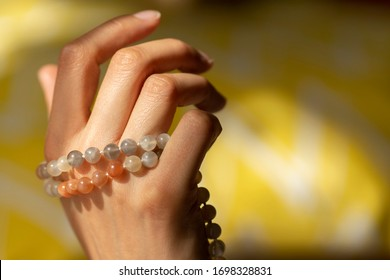Close-up of a woman's hand wearing colorful mala beads bracelet in the soft and warm light of the sun on a yellow blurry background.