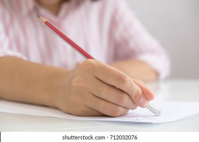 Closeup of woman's hand writing on paper. Close up of lady's hand writing in notepad placed on desktop with other items.