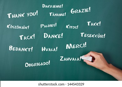 Closeup of woman's hand writing Thank You in various languages on chalkboard